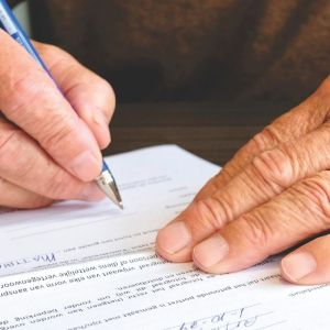 White hands signing a contract.