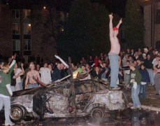 A rioter stands on top of a smashed and burned out car at Cedar Village Apartments in East Lansing, Mich., early Sunday morning as Michigan State University fans reveled following MSU's loss to Duke University in the Final Four in St. Petersburg, Fla.(AP Photo/Devon Akmon,The State News)