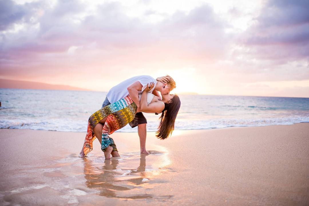 romantic kiss at sunset on beach in maui, hawaii