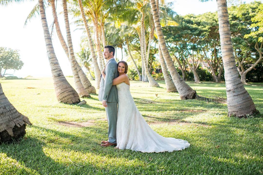 bride hugging her groom, standing behind him