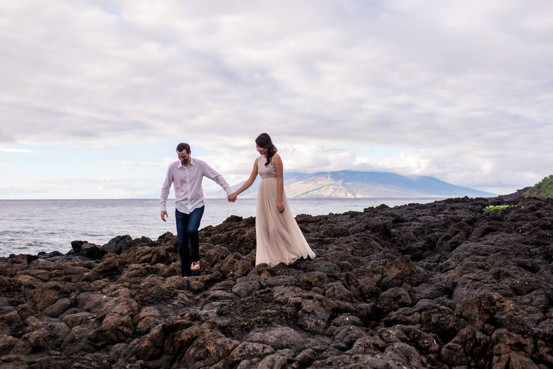 couple traversing lava rock together hand in hand