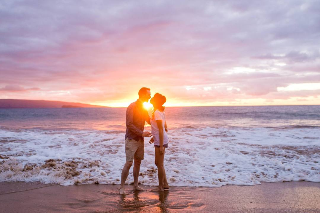engaged couple kissing, the sunset in between them