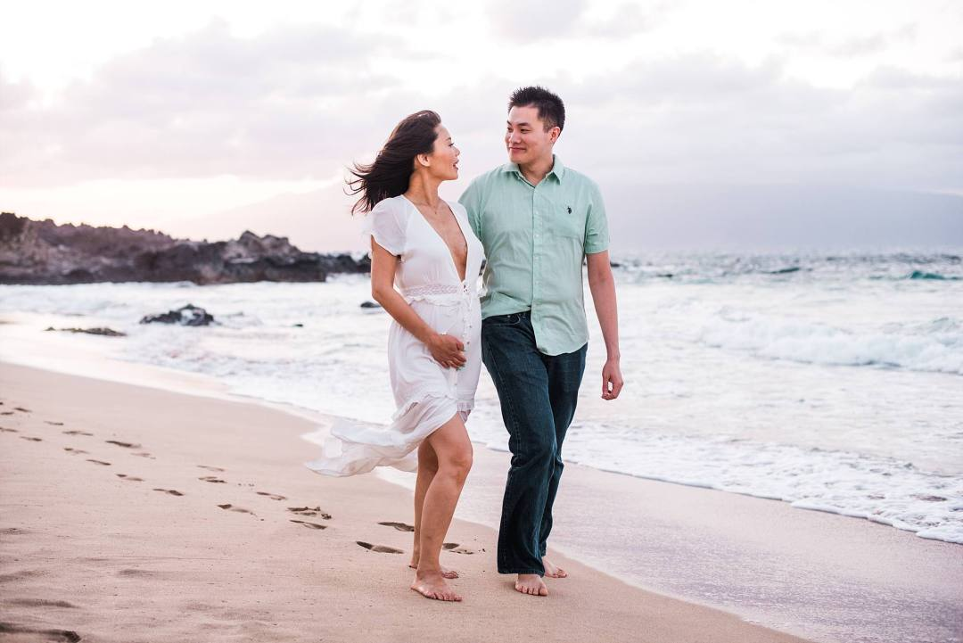 woman expecting walking closely with her husband down the beach