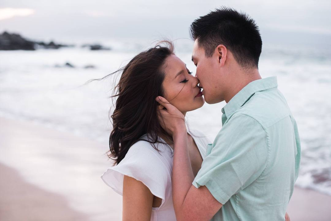 windswept maternity photo of loving couple kissing