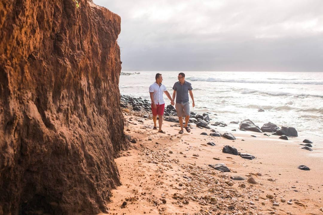 sweethearts holding hands walking on beach near beautiful rock wall