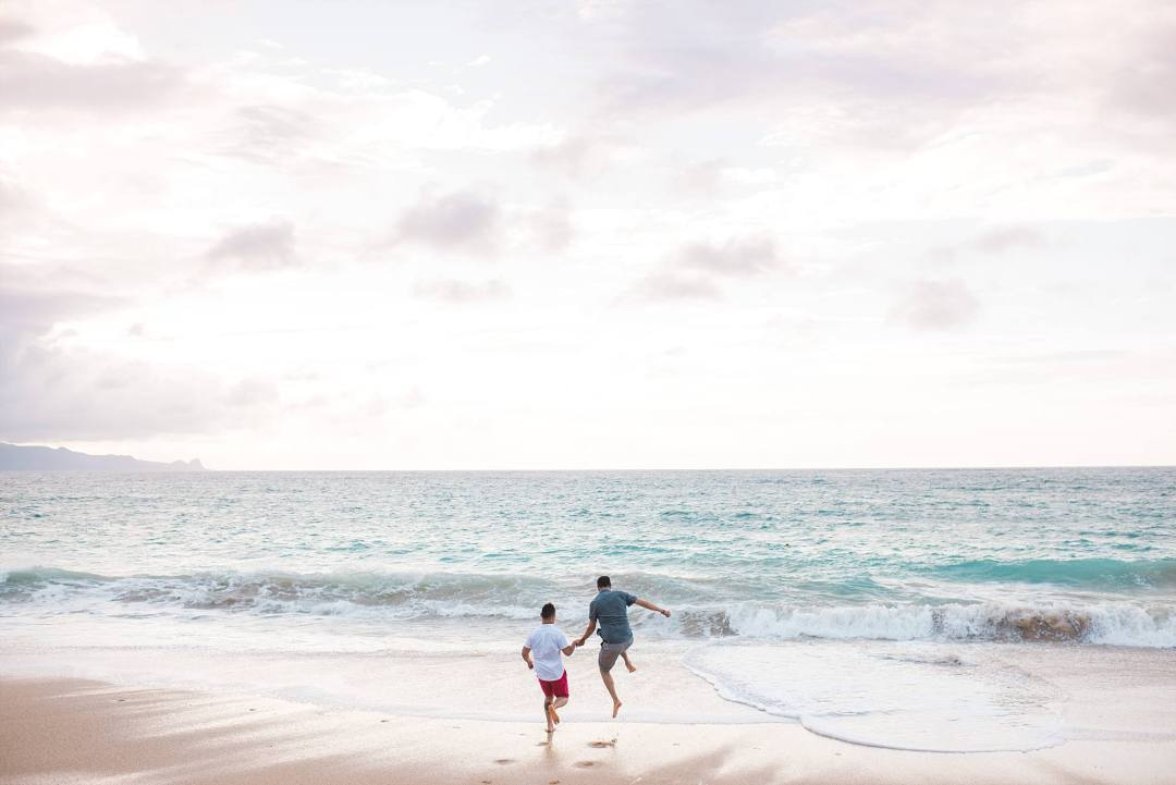 adventurous engaged couple jumping into the Pacific ocean together