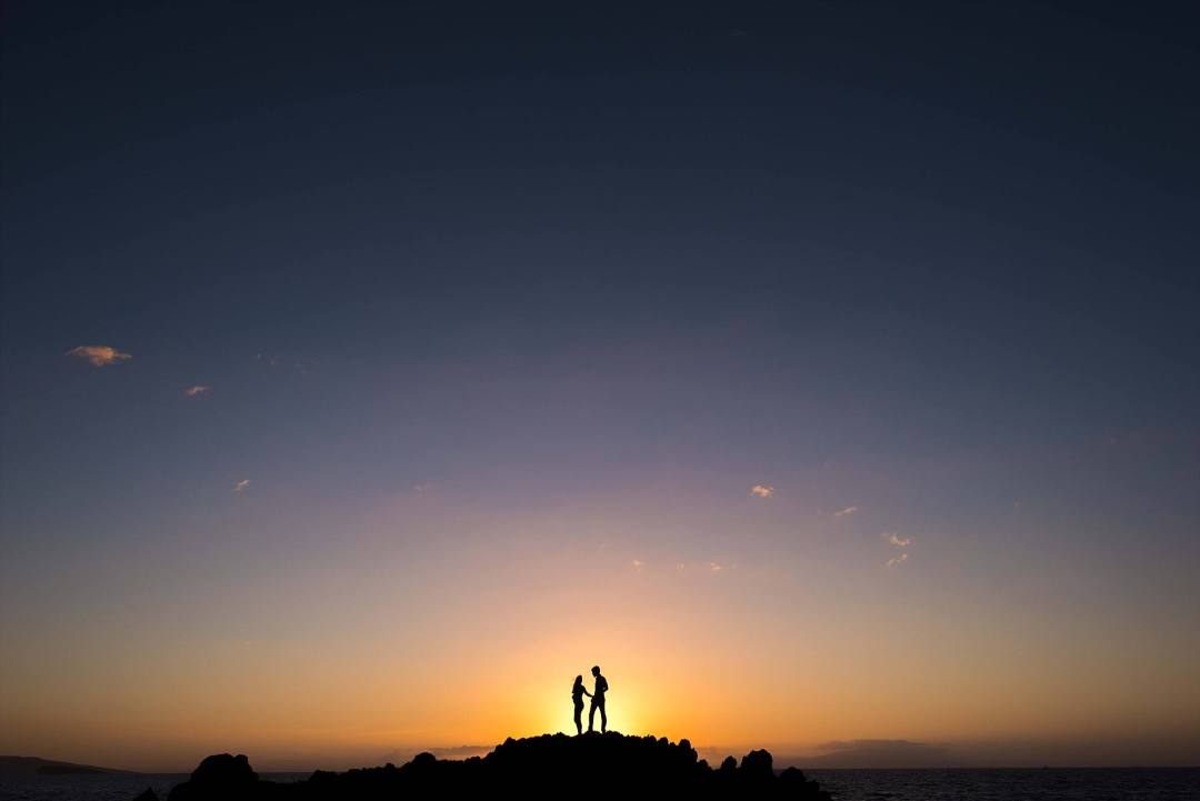 Maui sunset as back lighting for this couple's maternity shoot. Silhouettes on lava rock