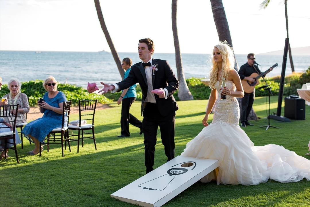 newly married couple playing bags provided by Bliss at their cocktail hour, location right on ocean