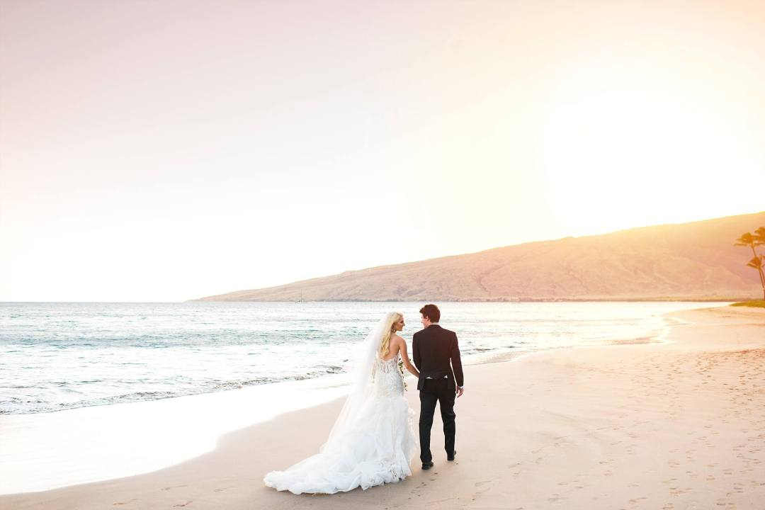 newly married couple walking down beach towards West Maui Mountains, beautiful wedding dresss flowing behind the bride