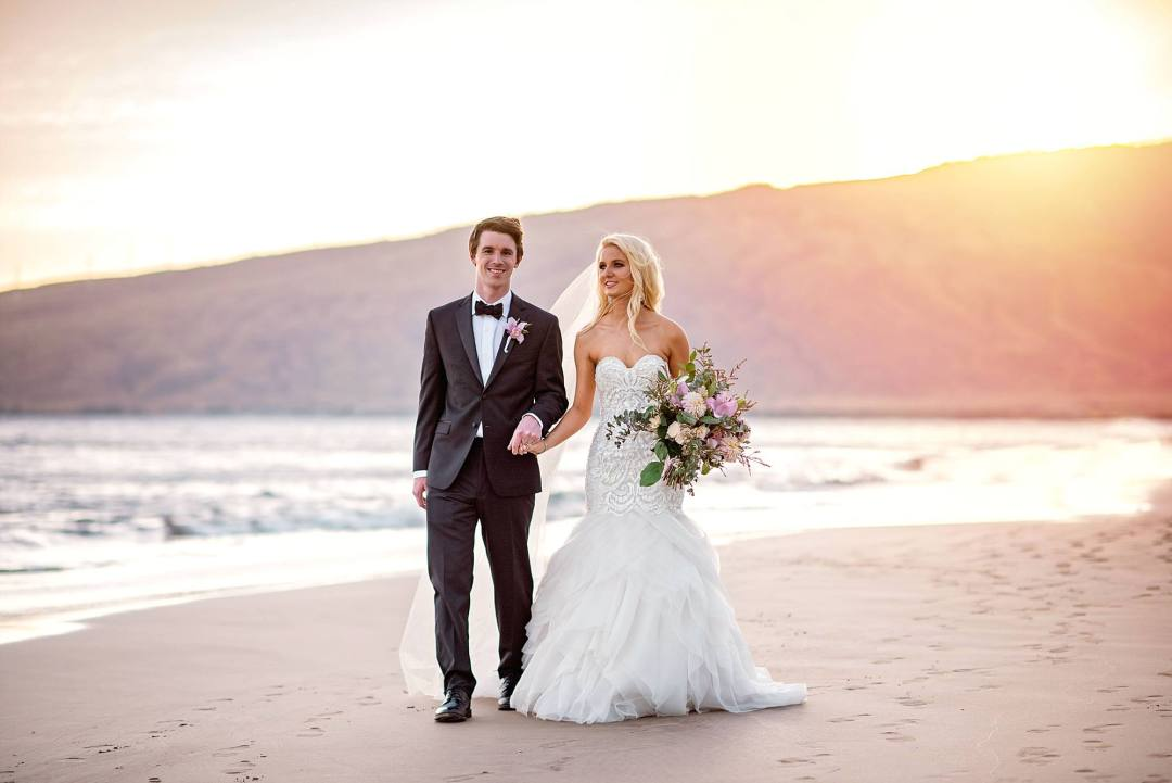 bride gazing at her husband holding hands on white sand beach of Maui with sun dipping behind mountains