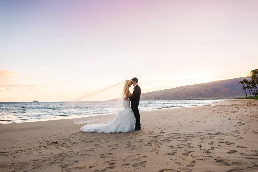 wedding couple standing together hand in hand in South Maui at sunset