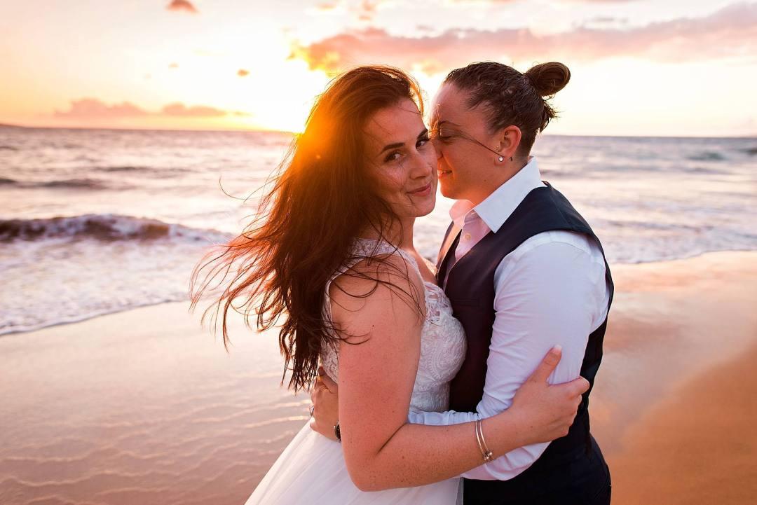 gay couple cuddling on beach in maui