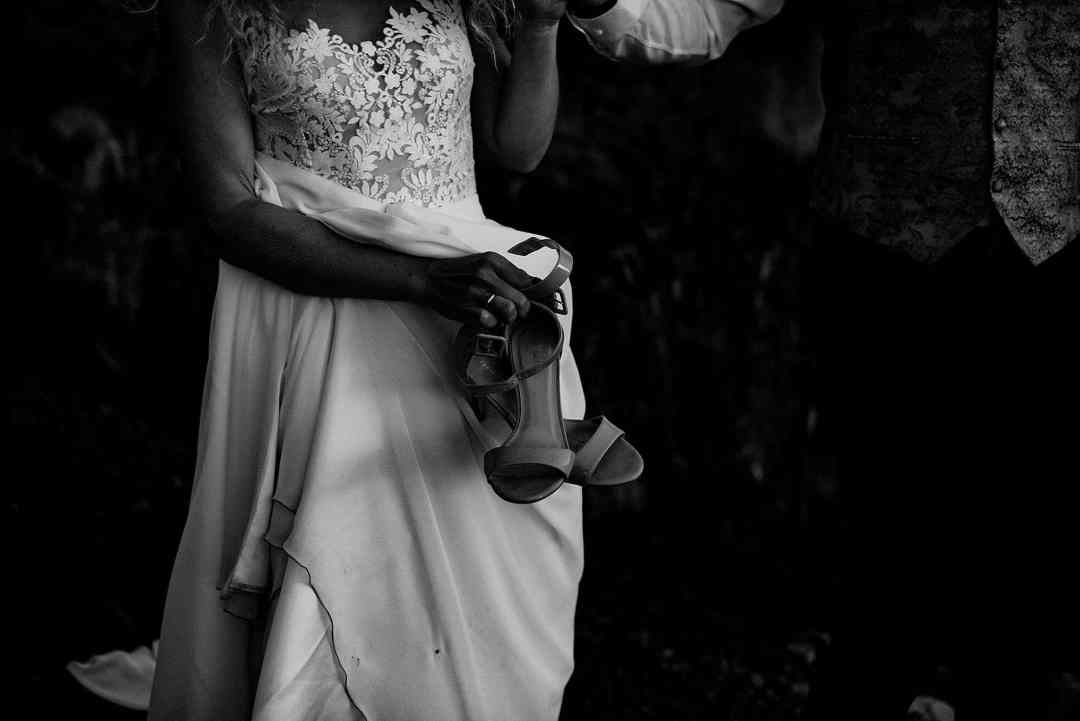 bride carrying shoes