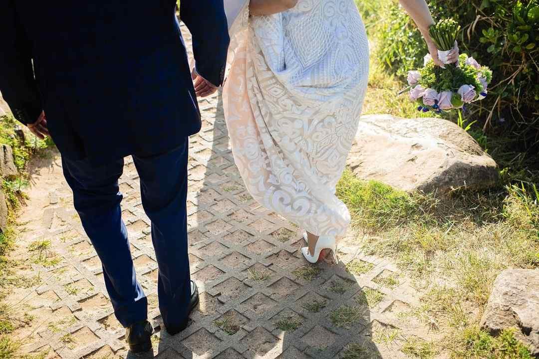 bride walking in heels at the beach