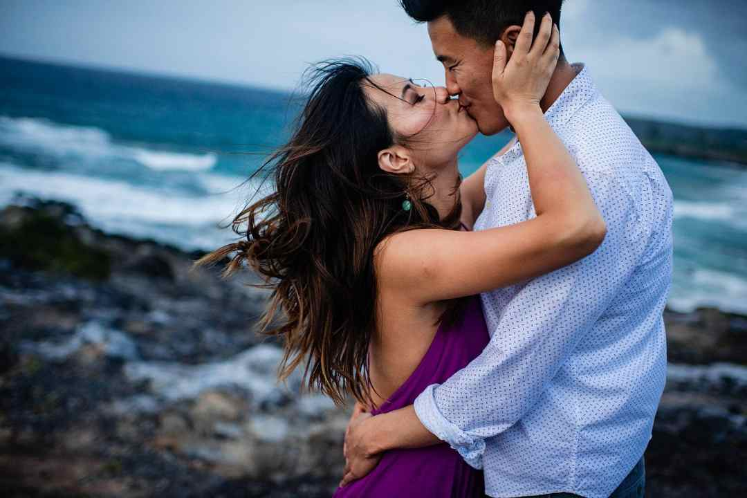 couple kissing on cliff in maui