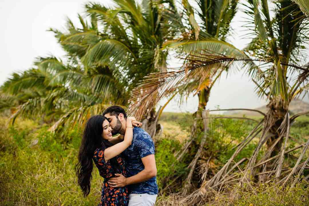 couple kissing with palm trees