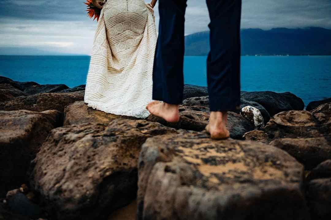 bride and groom walking out to ocean on rocks