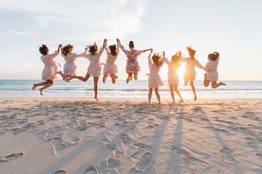Bridesmaids jumping on beach