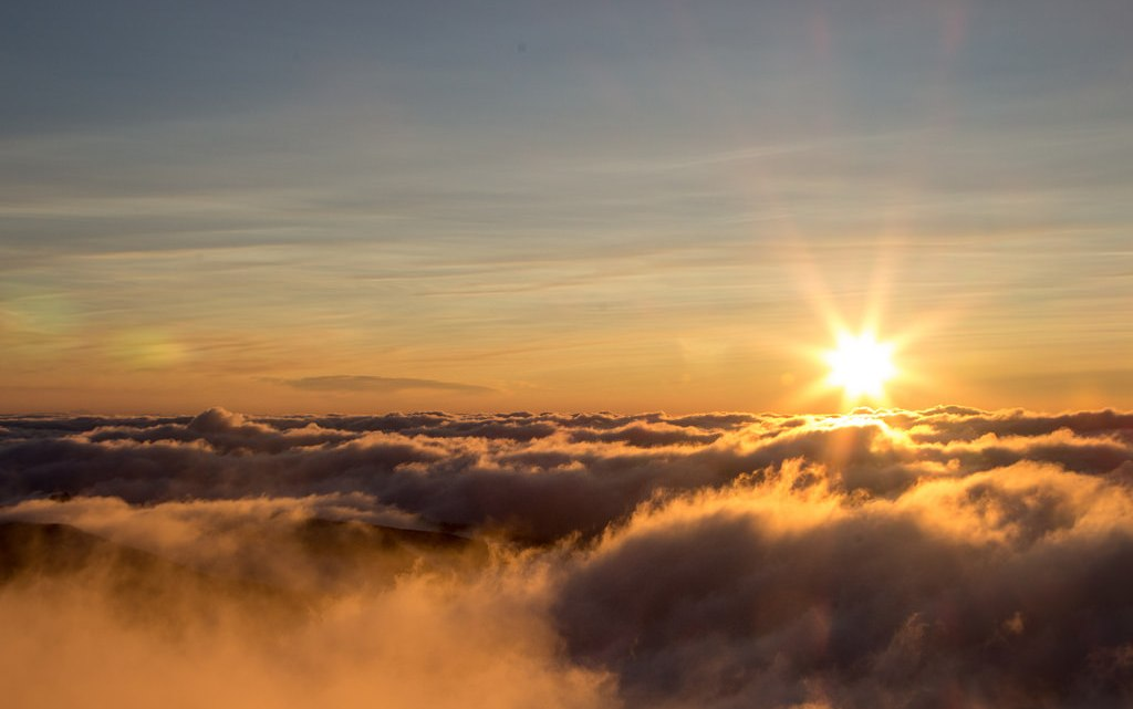 high elevation with sun rising over a cloud layer