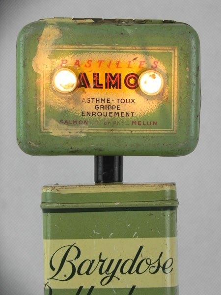 """Barydose. Robot lumineux avec deux boites de médicaments """"Salmon"""" et """"Barydose"""", sur deux poignées de robinet en porcelaine."""
