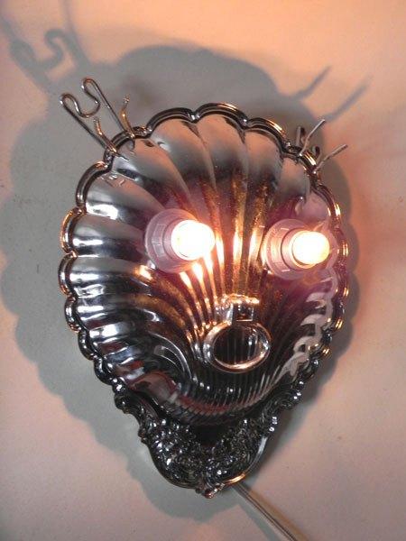 Biglion. Trophée lumineux tête de lion avec un plat de présentation en forme de coquille, une poignée et deux crochets. Lampe applique.