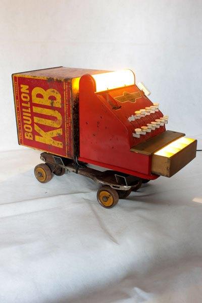 Caiskub. Camion rouge KUB assemblage d'une caisse enregistreuse pour enfants et d'une boite de bouillon KUB, sur deux patins à roulettes.