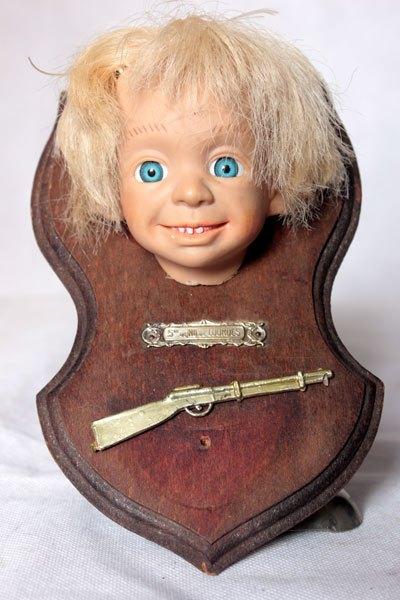 """Carabeni, Assemblage improbable: poupée, fusils et bénitier. Détournement d'une tête de poupée, fusil en plastique, plaque de bénitier """"Notre dame de Lourdes""""."""