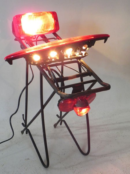 Cibm. Assemblage lumineux morceaux d' auto moto vélo, feu arrière sur une structure porte bagage. Rouge et noir.