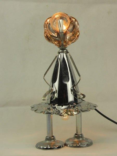 Coutielle. Sculpture assemblage lumineux métal. Composition: coupe de sport, coupe en verre, supports de porte serviettes, assiette de présentation, pince à escargot.