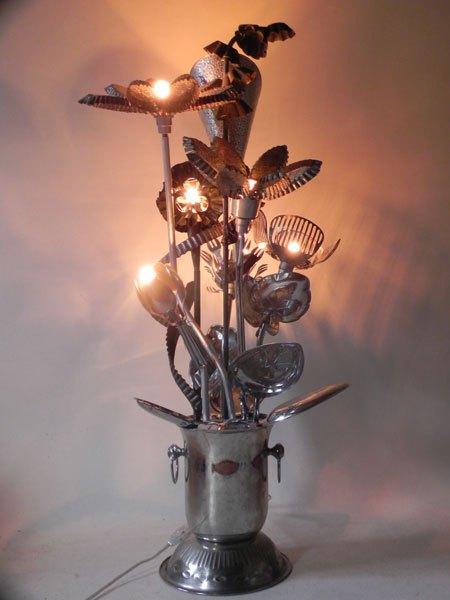 FleurMetal. Composition florale en moules et ustensiles de cuisine. Assemblage lumineux avec un sceau à champagne, des moules à pâtisserie...