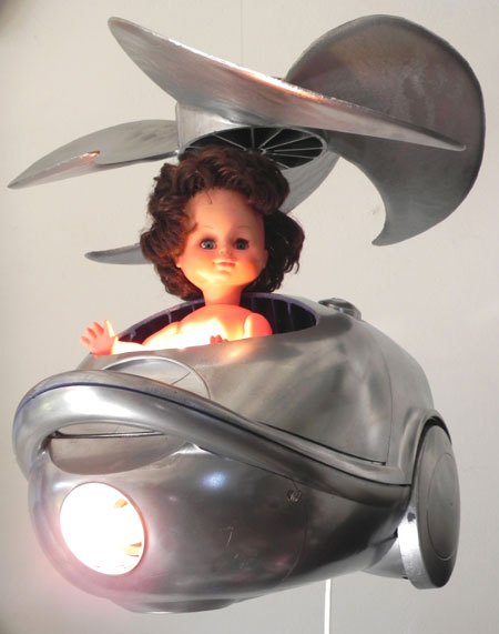 Helirateur. Détournement d'aspirateur en hélicoptère. Assemblage, recyclage lumineux, composé d'un aspirateur cassé, une hélice et une poupée.