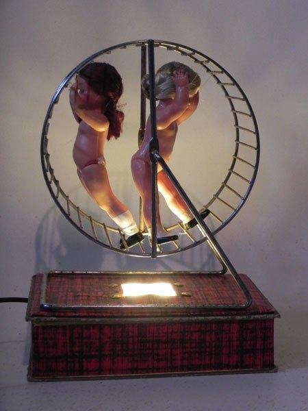 LaRoue. Poupées dans une roue de hamster sur une jolie boite qui les éclaire. Association d'objets, association d'idées.