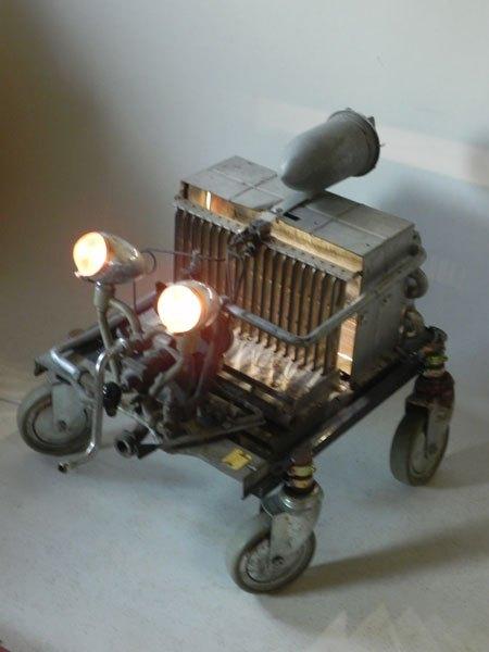 Luxorbain. Sculpture véhicule spatial recyclage lumineux. Assemblage d'un intérieur de chaudière sur roulettes, un moteur d'aspirateur et deux optiques de vélo ancien en aluminium.