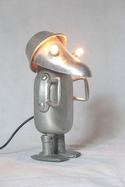 Manalu4. Bonhomme lumineux en aluminium détourné. Assemblage d'un embauchoir, un flacon, un moule, deux poignées de fenêtre et deux anses.
