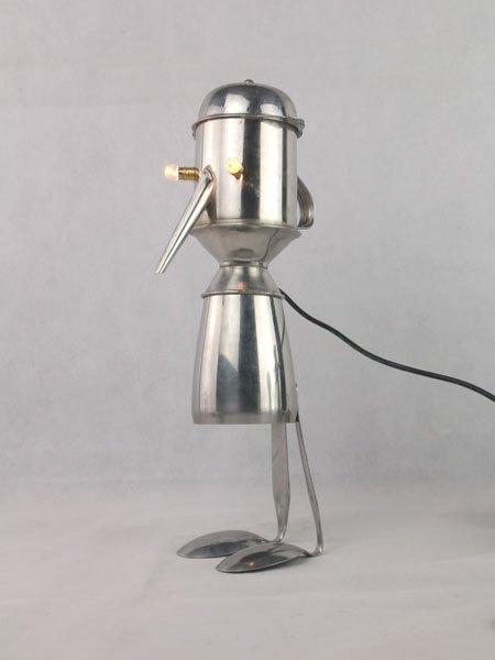 Moninox. Sculpture personnage avec des objets en inox. Lampe. Assemblage: tasse, burette, ramequin, 2 cuillères.