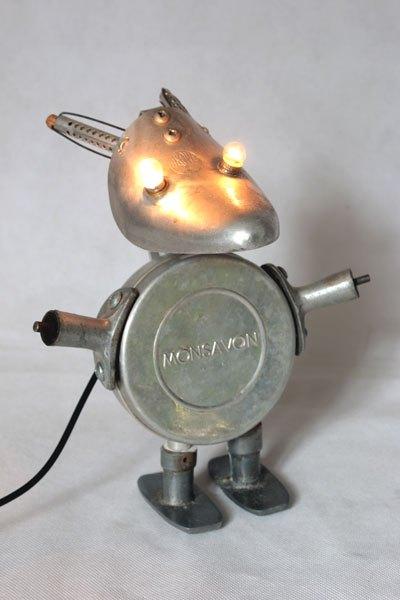 """Monsavon3. Sculpture lumineuse en aluminium. Assemblage d'un embauchoir, une boite à savon """"Monsavon"""", deux poignées de fenêtre et de casserole et deux bigoudis ."""