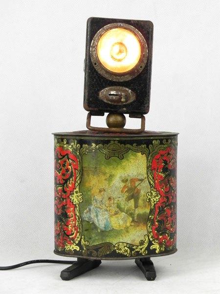 Nomant. Assemblage lumineux lampe de poche et boite en métal imprimée ancienne, pied en frein de vélo.