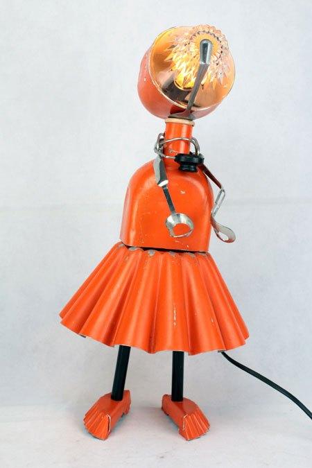 Orangour. Fille orange avec gourde et moule à gâteaux. En métal peint, aluminium, verre, inox et plastique.