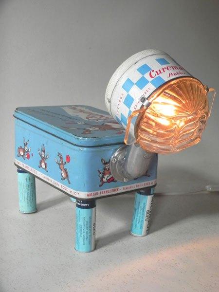 """Patachou. Animal lumineux à quatre pattes avec boites anciennes. Composition: boite à chaussure """"patachou"""", boite """"curemail"""", 4 tubes de médicament, bol en verre."""