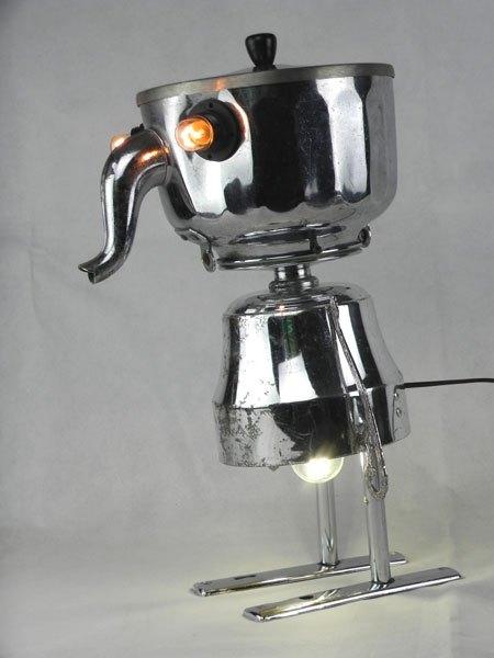 Porboupe. Sculpture objets de cuisine. Assemblage lumineux d'unebouilloire, une coupe de sport, un couvercle et deux plaques de porte.