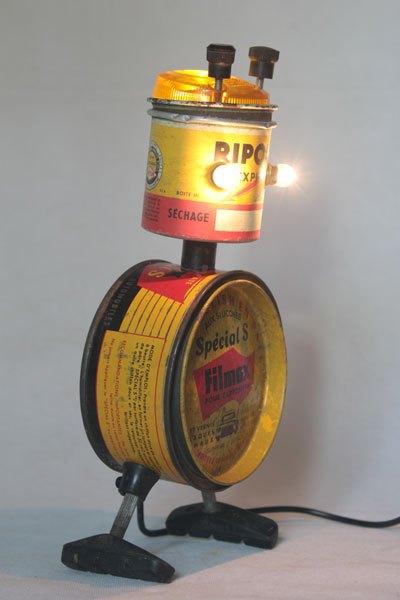 """Ripolex. Robot insecte avec des boites vintages. Assemblage """"Ripolin express, séchage rapide"""" et """"Filmex pour carrosserie, super polish en pâte aux silicones"""", avec cabochon lumineux et freins de vélo."""