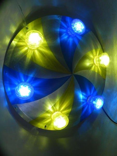 soucou5. Applique soucoupe volante festive. Composition: cône peint en bleu et jaune, ampoules de fête foraine bleues et jaunes .