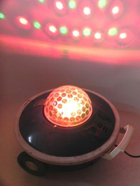 soucoupe. Soucoupe lumineuse aspirateur bleu sur roulettes, jeux de lumière intégré.
