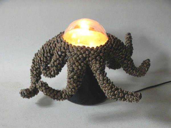 Tentapin. Sculpture lumineuse avec tentacules de pommes de pin. Pommes de pin démontées, recomposées en tentacules autour d'un verre de cafetière.
