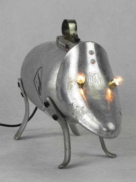 """Toutouta. Sculpture chien lumineux en aluminium recyclé. Assemblage d'une gourde, un embauchoir """"ABOVE"""" et quatre pieds de passoire."""