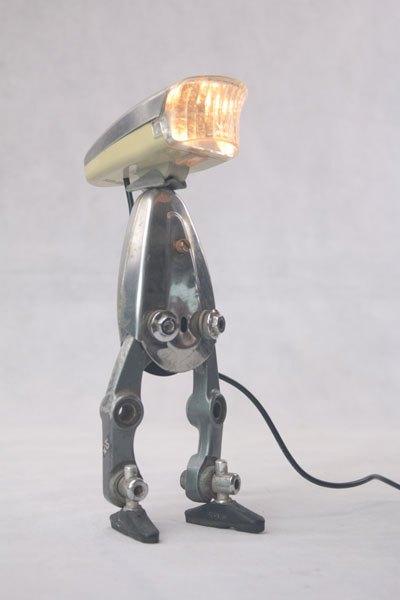 Veloboyp1. Personnage lumineux avec optique de vélo sur étrier de frein . inox, plastique.