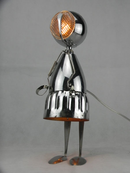 Coupline. Assemblage fille, lampe en métal avec une coupe de sport, une coupelle en verre, trois cuillères et une pince à escargot.