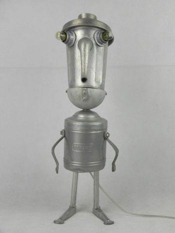 Sculpture par assemblage d'objets de cuisine en aluminium. Composition: cafetière, couvercle, poignées, tendeur de tennis, pot à farine, louche.