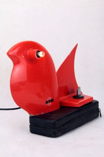 Oiseau rouge boucherie. Assemblage de pièces de trancheuse à jambon sur housse de rasoir électrique.
