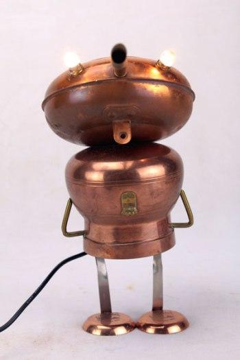 """Sculpture assemblage ustensiles cuivre. Personnage avec un petit faitout, une bouilloire ,2 mini poêles """"la mère Poulard""""."""